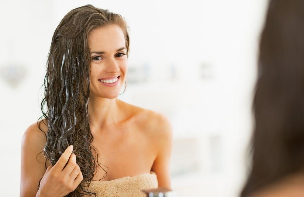 woman using leave-in conditioner on her hair